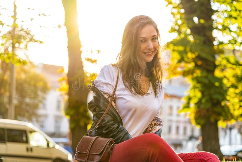 Szczęśliwa dziewczyna jest siedząca i ono uśmiecha się outdoors Styl życia fotografia z młodą piękną kobietą zdjęcia royalty free