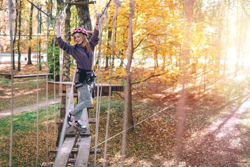 Szczęśliwa dziewczyna, kobieta, wspina się przekładnię w przygodzie, linowa droga, ubezpieczenie, przyciąganie, park rozrywki, ak fotografia royalty free