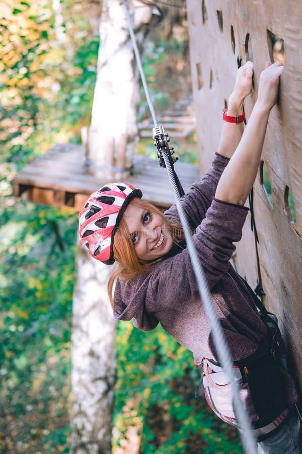 Szczęśliwa dziewczyna, kobiety, wspina się przekładnię w przygoda parku angażuje w rockowym pięciu na linowej drodze, arboretum,  zdjęcia stock
