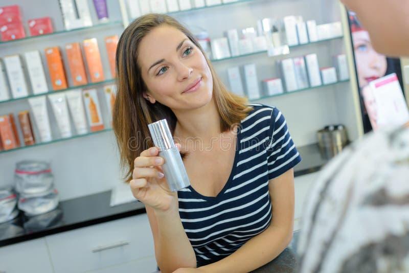 Szczęśliwa dziewczyna kupuje cosmetical śmietankę w zakupy centrum handlowym obrazy royalty free
