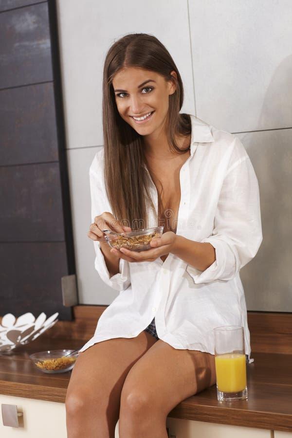 Szczęśliwa dziewczyna ma śniadanie w kuchni obraz royalty free