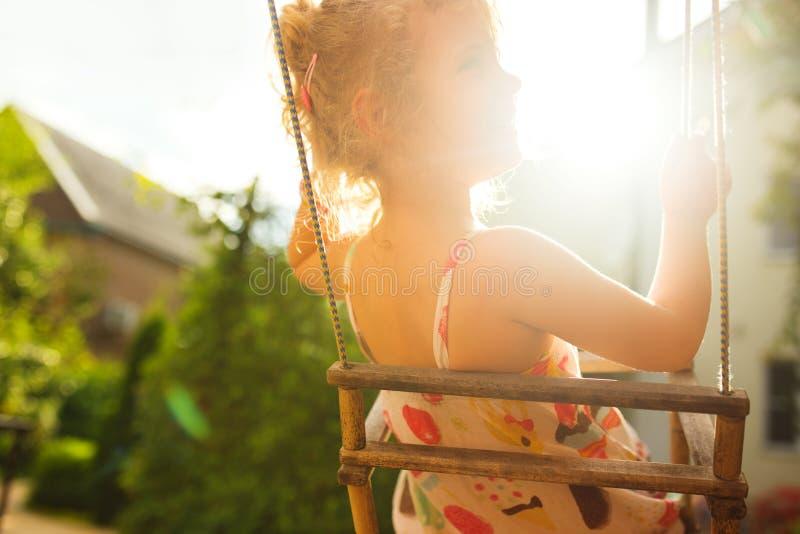 Szczęśliwa dziewczyna ma zabawę na huśtawce na letnim dniu fotografia stock