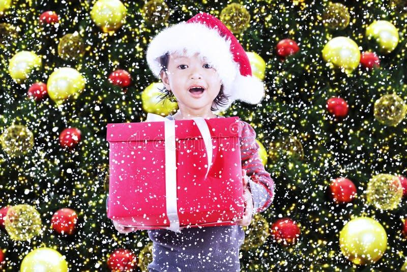 Szczęśliwa dziewczyna otrzymywa boże narodzenie prezent pod drzewem obraz royalty free
