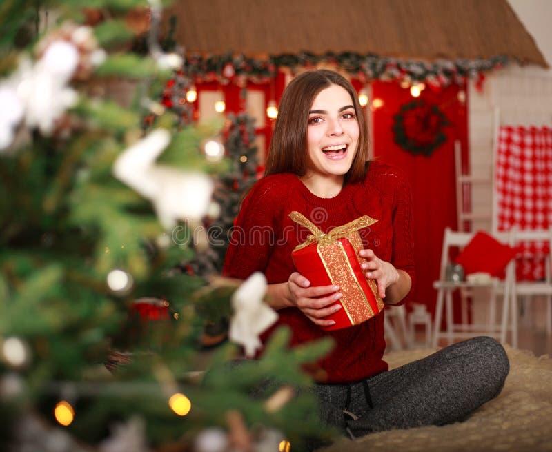 Szczęśliwa dziewczyna otwiera prezent w wakacje na wigilii w domu zdjęcia stock