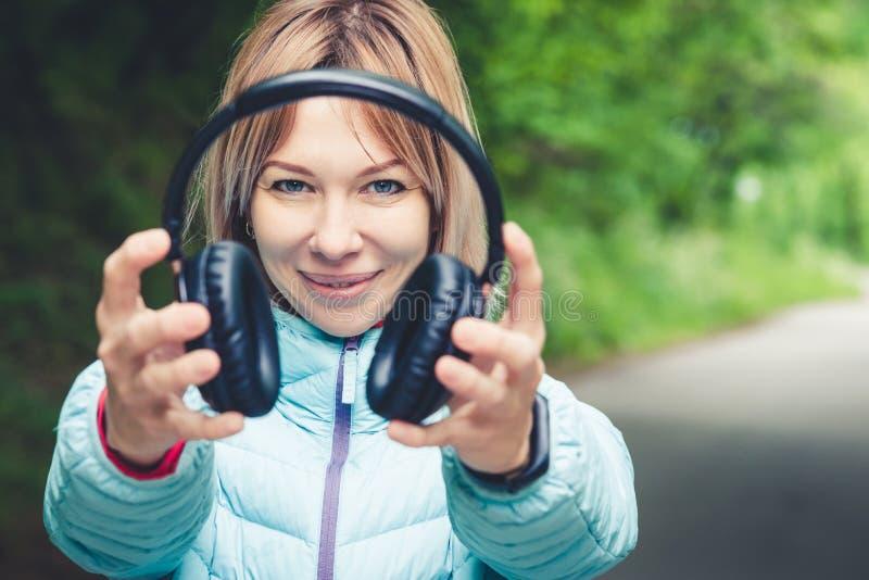 Szczęśliwa dziewczyna outdoors w lesie trzyma hełmofony Pojęcie stereo muzyka gdziekolwiek Chodząca muzyka zdjęcia stock