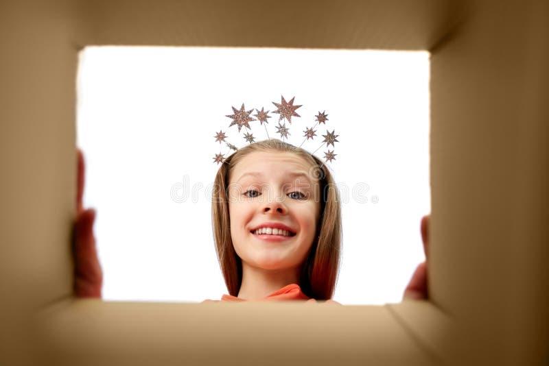 Szczęśliwa dziewczyna patrzeje w otwartego prezenta pudełko w tiarze zdjęcie royalty free