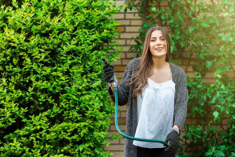 Szczęśliwa dziewczyna plenerowa w podwórku, uprawia ogródek jako hobby fotografia royalty free