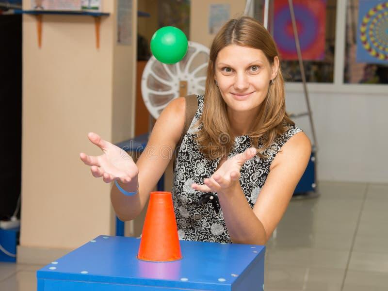 Szczęśliwa dziewczyna przy eksponatem z latającą piłką w muzeum zabawna nauka Einstein zdjęcia royalty free