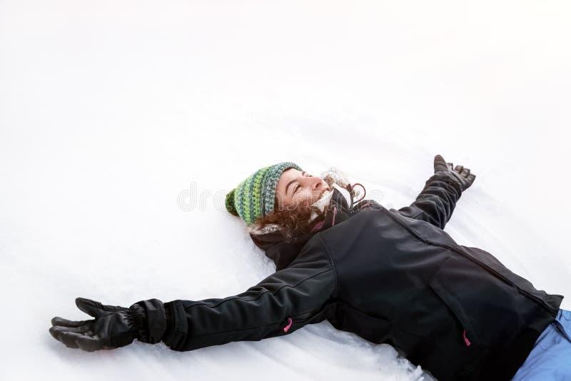 Szczęśliwa dziewczyna robi śnieżnemu aniołowi zdjęcie royalty free