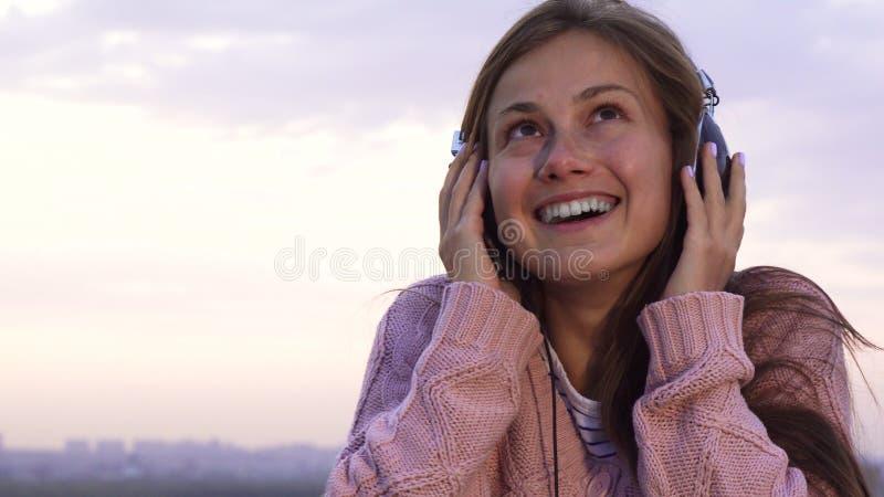 Szczęśliwa dziewczyna słucha muzyka z hełmofonami stoi na dachu obraz stock
