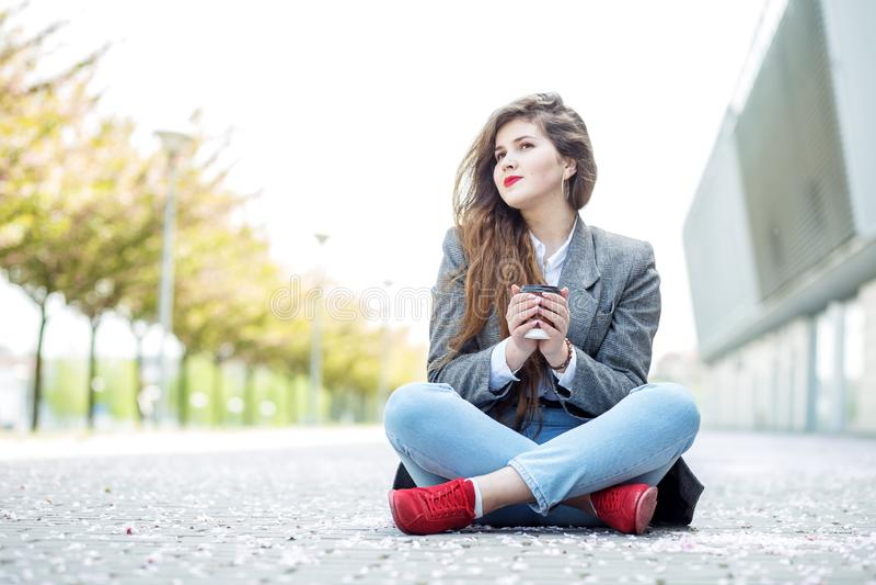 Szczęśliwa dziewczyna siedzi na podłodze z kawą i marzy Poj?cie styl ?ycia, miastowy, czas wolny, ucznie obrazy stock