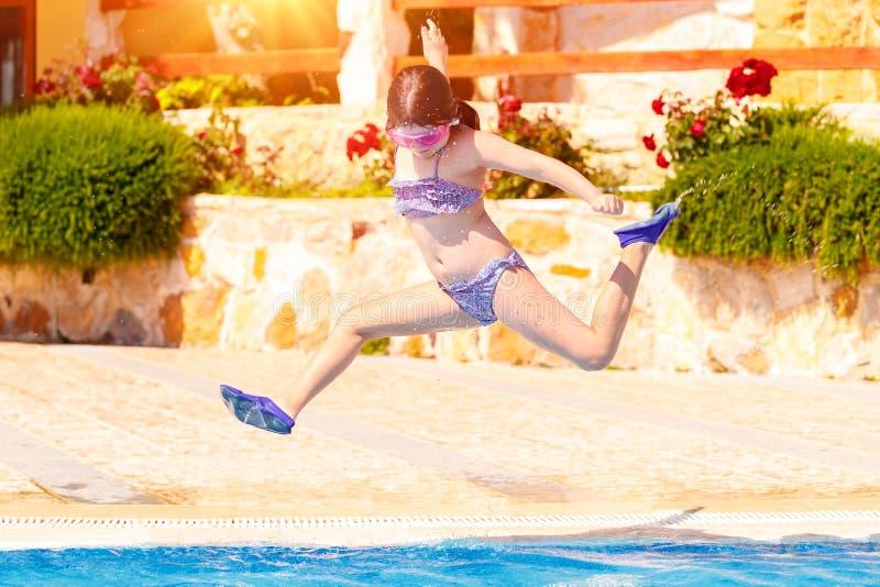 Szczęśliwa dziewczyna skacze basen zdjęcie stock