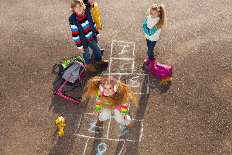Szczęśliwa dziewczyna skacze hopscotch zdjęcia royalty free