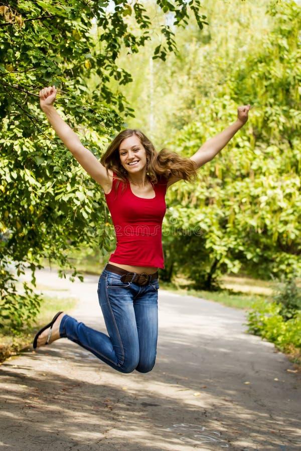 Szczęśliwa dziewczyna skacze outdoors fotografia royalty free
