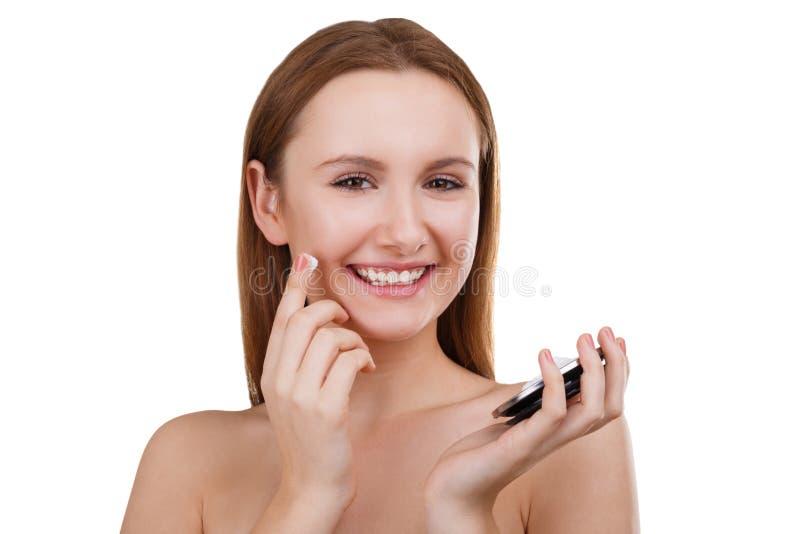 Szczęśliwa dziewczyna stosuje kosmetyczną śmietankę na twarzy i ono uśmiecha się pojedynczy białe tło zdjęcia royalty free