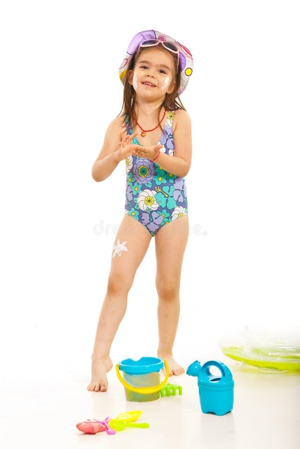 Szczęśliwa dziewczyna stosuje sunblock płukankę zdjęcie royalty free