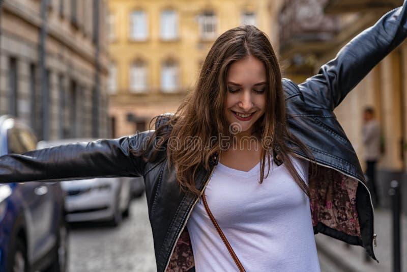 Szczęśliwa dziewczyna tanczy w starym mieście Uliczny mody sesja zdjęciowa. z pięknym kobieta modelem obrazy royalty free