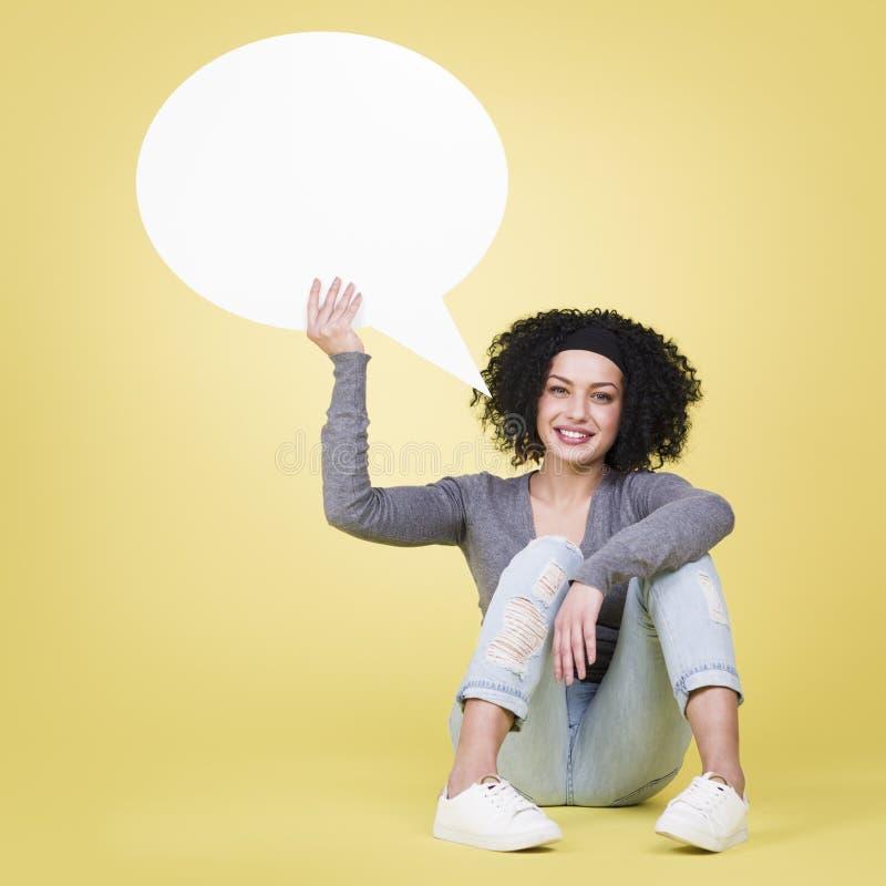 Szczęśliwa dziewczyna trzyma pustego mowa balon z kopii przestrzenią obraz stock