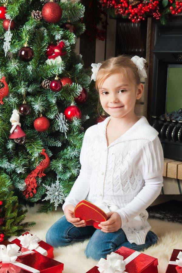Szczęśliwa dziewczyna w białej kurtce z prezentem blisko choinki fotografia stock