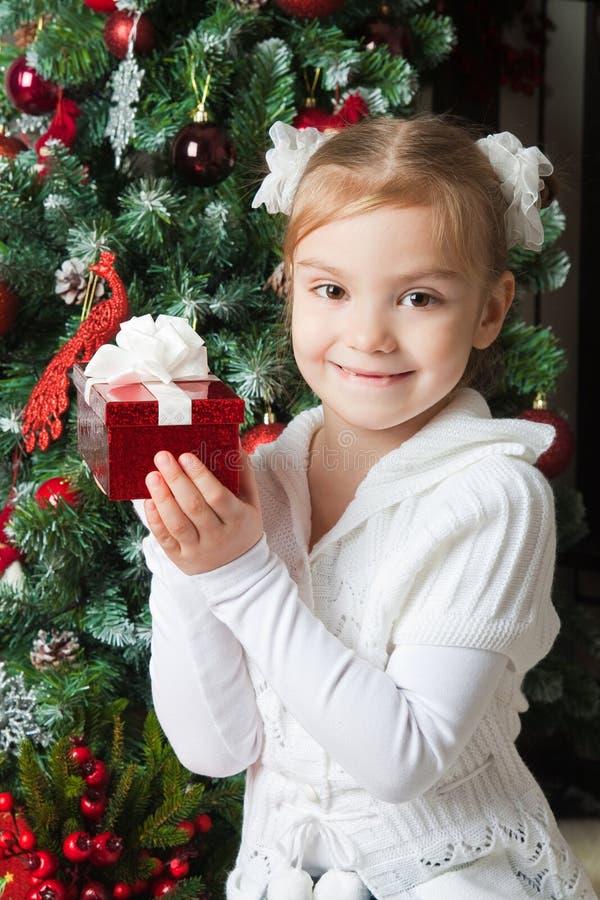 Szczęśliwa dziewczyna w białej kurtce z prezentem blisko choinki zdjęcia stock