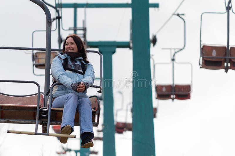 Szczęśliwa dziewczyna w kurtce iść na chairlift obraz stock