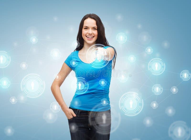 Szczęśliwa dziewczyna wskazuje przy ogólnospołeczną siecią w koszulce zdjęcie stock