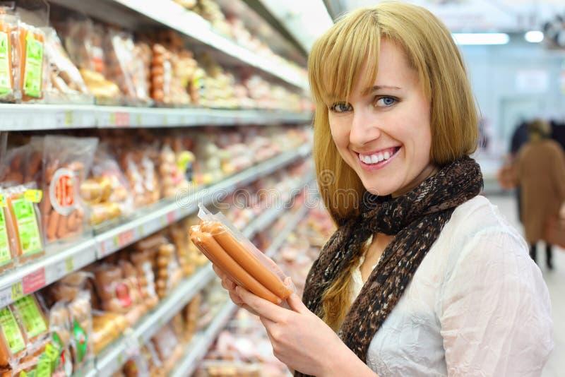 Szczęśliwa dziewczyna wybiera kiełbasę w sklepie zdjęcie royalty free