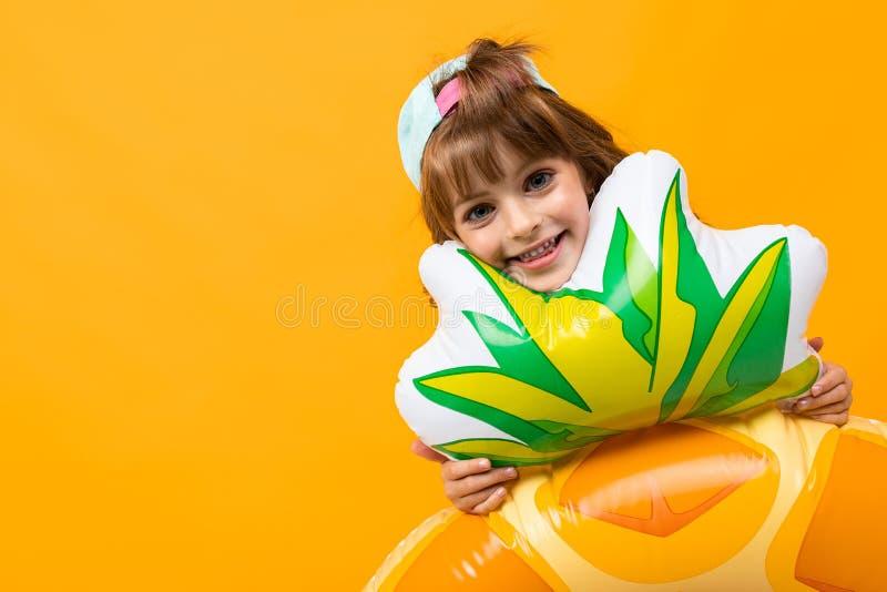 Szczęśliwa dziewczyna z czapką baseballową w stroju kąpielowym z gumowym pierścieniem ananasowym na pomarańczowym tle obraz royalty free