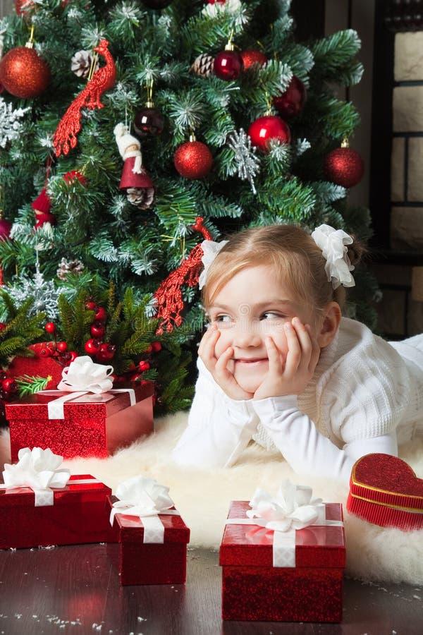 Szczęśliwa dziewczyna z giftslying blisko choinki obraz stock