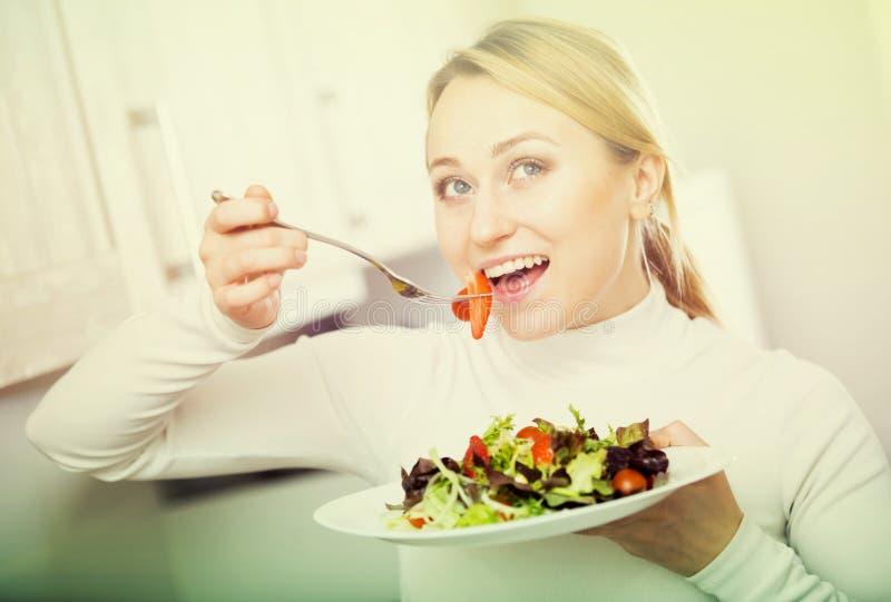 Szczęśliwa dziewczyna z jarzynową sałatką w kuchni obrazy stock