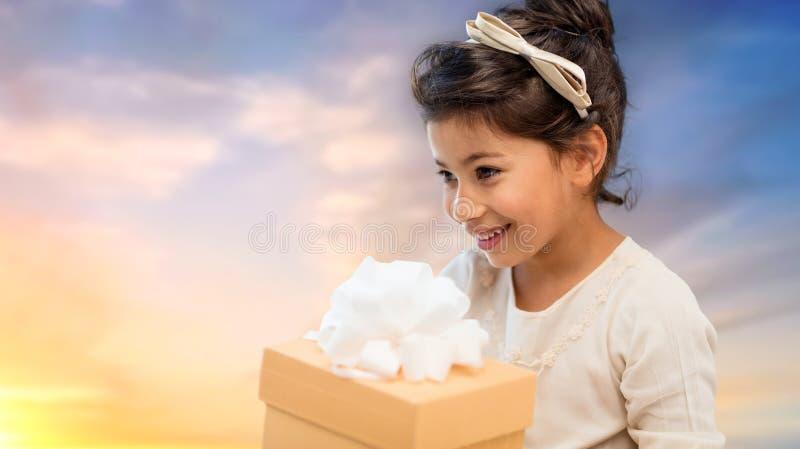 Szczęśliwa dziewczyna z prezenta pudełkiem nad wieczór niebem obrazy stock