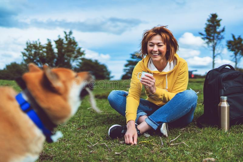 Szczęśliwa dziewczyna z uśmiechu napoju filiżanką bawić się z czerwonym japończyka psa shiba inu na zielonej trawie w outdoors na zdjęcie royalty free