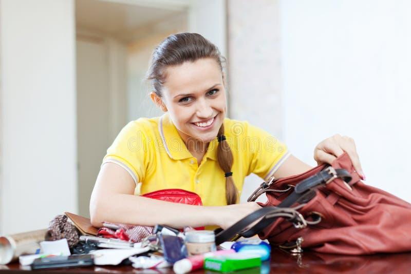 Szczęśliwa dziewczyna zakładająca rzecz w torebce fotografia stock