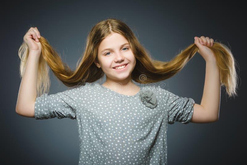 szczęśliwa dziewczyna Zbliżenie portreta dziecka przystojny ono uśmiecha się odizolowywam na popielatym fotografia stock
