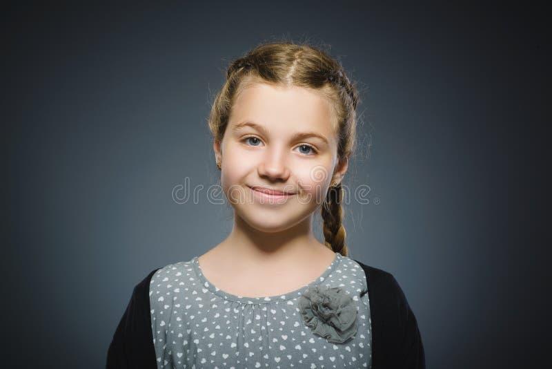 szczęśliwa dziewczyna Zbliżenie portreta przystojny dziecko ono uśmiecha się na popielatym fotografia stock