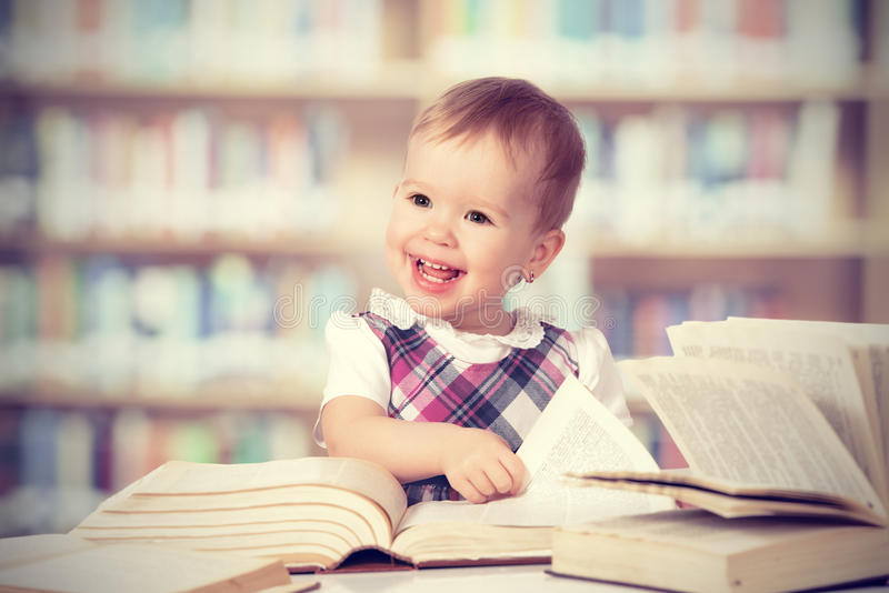 Szczęśliwa dziewczynka czyta książkę w bibliotece obrazy stock