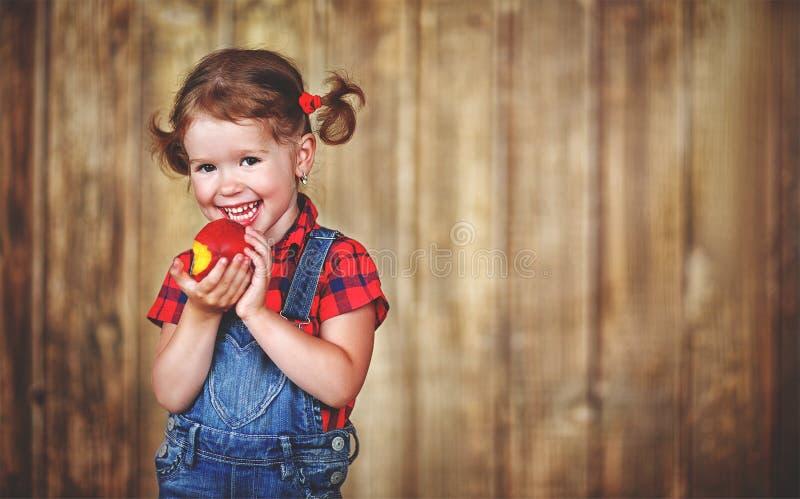 Szczęśliwa dziewczynka je dojrzałą brzoskwinię obraz stock
