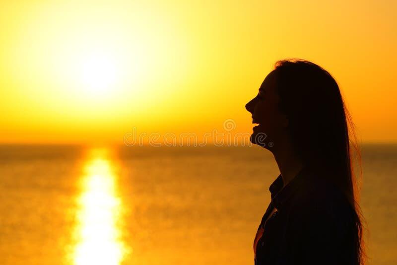 Szczęśliwa dziewczyny sylwetka kontempluje słońce przy zmierzchem fotografia royalty free
