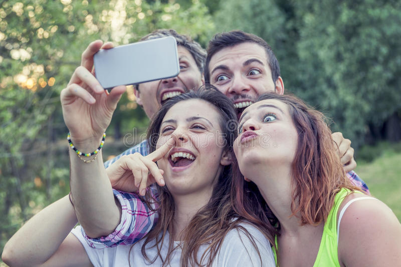 Szczęśliwa grupa młodzi ludzie bierze selfie obrazy stock