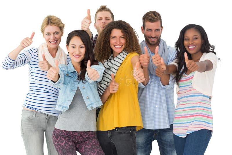 Szczęśliwa grupa młodzi przyjaciele daje kciukom do kamery zdjęcie stock