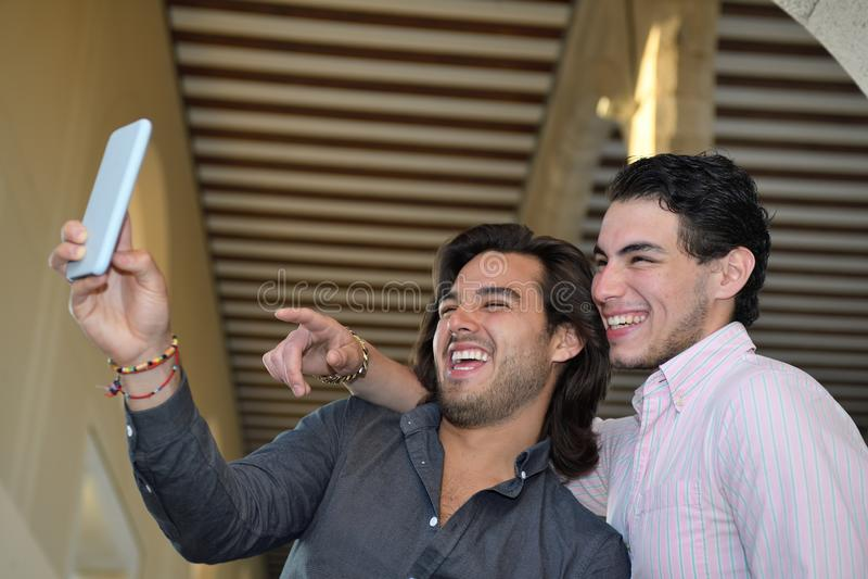 Szczęśliwa homoseksualna para bierze obrazki z ich telefonem komórkowym fotografia royalty free