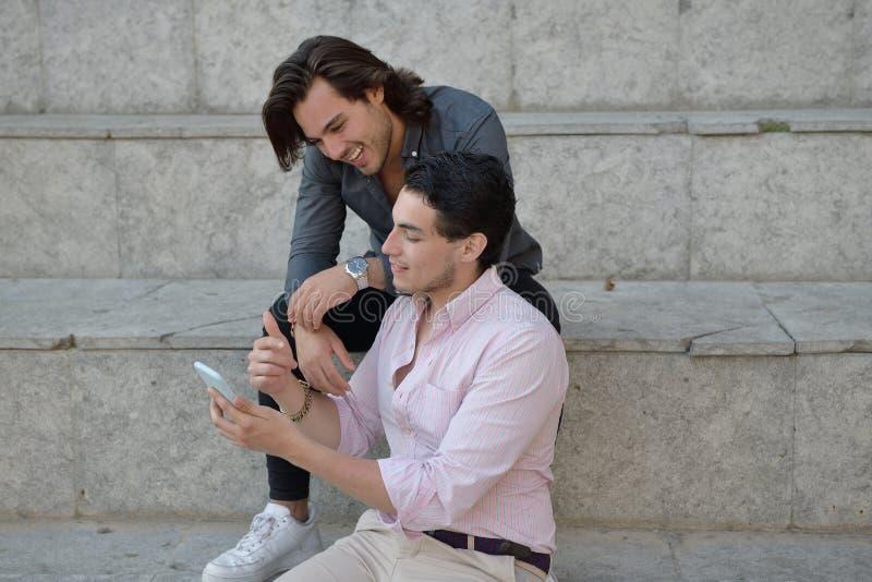 Szczęśliwa homoseksualna para z ich telefonem komórkowym fotografia royalty free