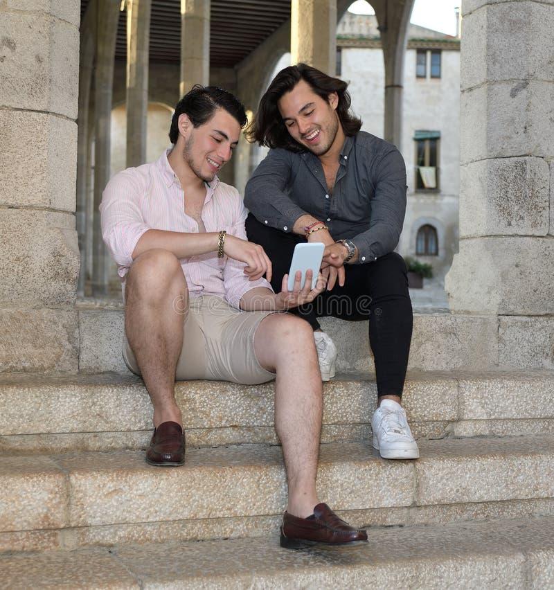 Szczęśliwa homoseksualna para z ich telefonem komórkowym zdjęcie stock