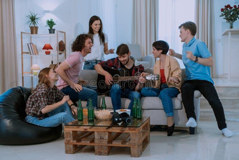 Szczęśliwa i atrakcyjna firma wielkiego czas wpólnie w przestronnym żywym pokoju one śpiewa na gitarze i dacing obrazy stock