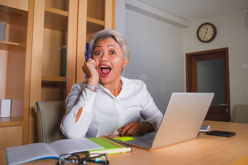 Szcz??liwa i pomy?lna atrakcyjna w ?rednim wieku Azjatycka kobieta pracuje przy biurow? laptopu biurka od?wi?tno?ci? zdjęcia stock
