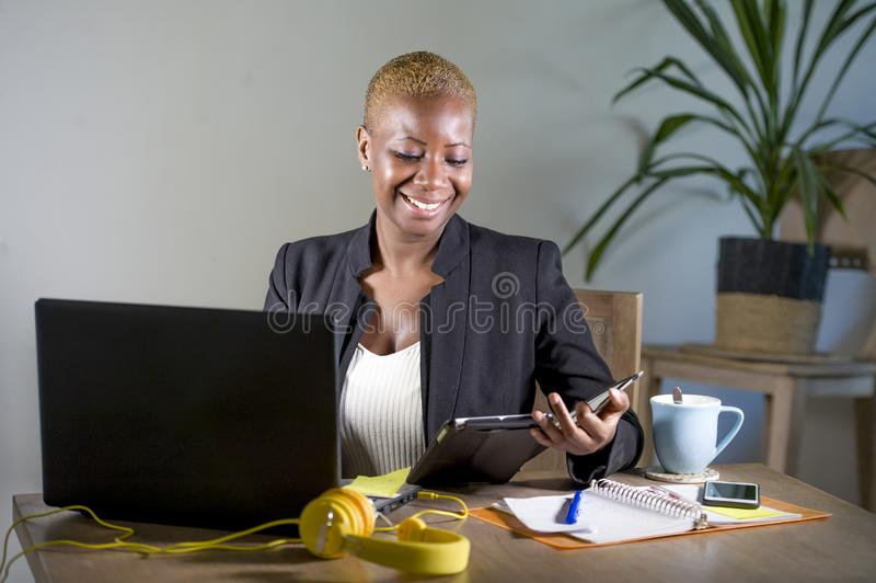 Szczęśliwa i pomyślna czarna afro Amerykańska biznesowa kobieta pracuje przy nowożytnym biurowym ono uśmiecha się rozochoconym uż fotografia royalty free
