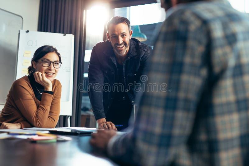 Szczęśliwa i pozytywna biznes drużyna w spotkaniu obraz stock