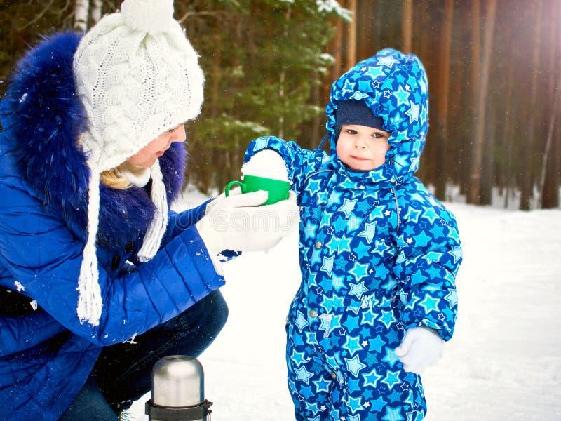 Szczęśliwa i radosna matka i dziecko na spacerze, sztuka w zima lasowym Sosnowym lesie Chelyabinsk region, Ural, Rosja zdjęcie stock