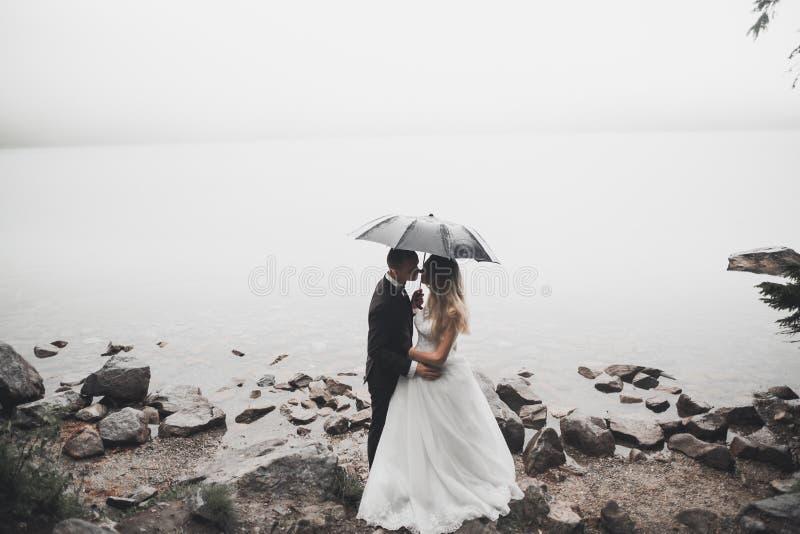 Szczęśliwa i romantyczna scena właśnie zamężna młoda ślub para pozuje na pięknej plaży zdjęcie stock
