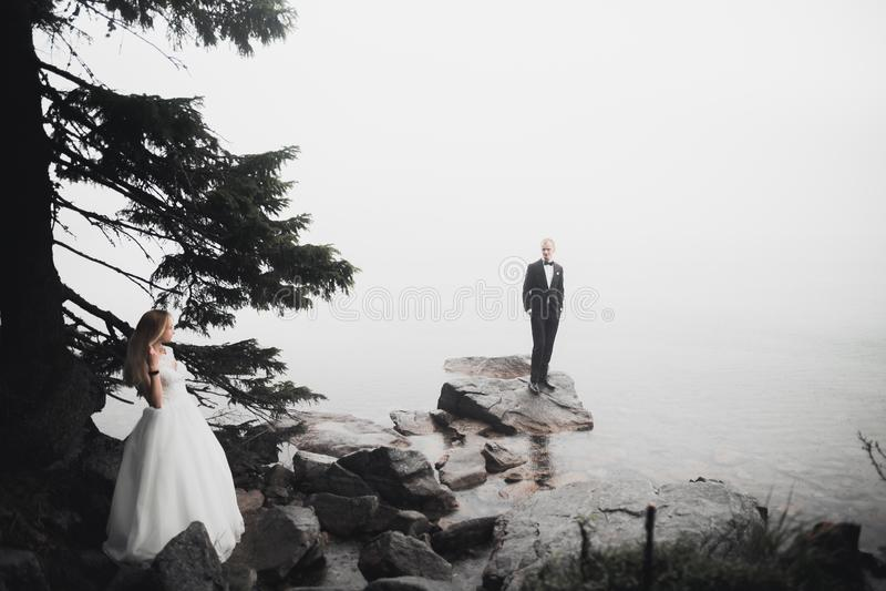 Szczęśliwa i romantyczna scena właśnie zamężna młoda ślub para pozuje na pięknej plaży fotografia royalty free